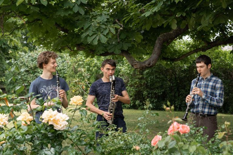 Trois jeunes hommes jouent de la musique dans le jardin du Foyer Les Enfants des Arts