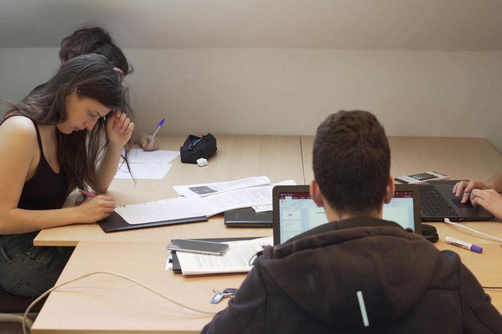 Trois étudiants en train de réviser dans une salle d'études