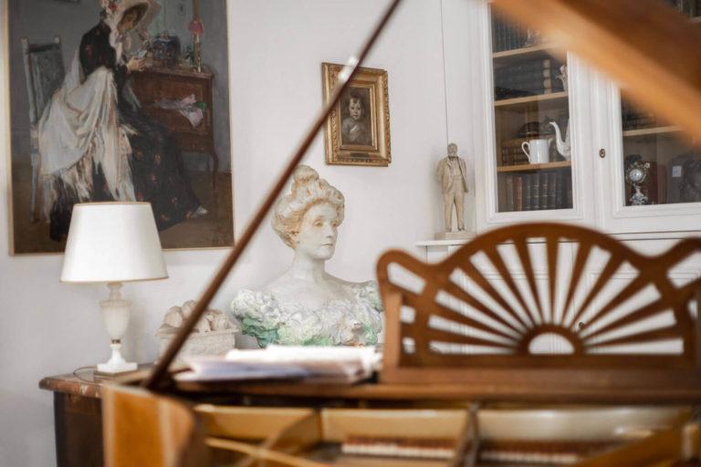 Salle comportant des tableaux, des sculptures et un piano à queue