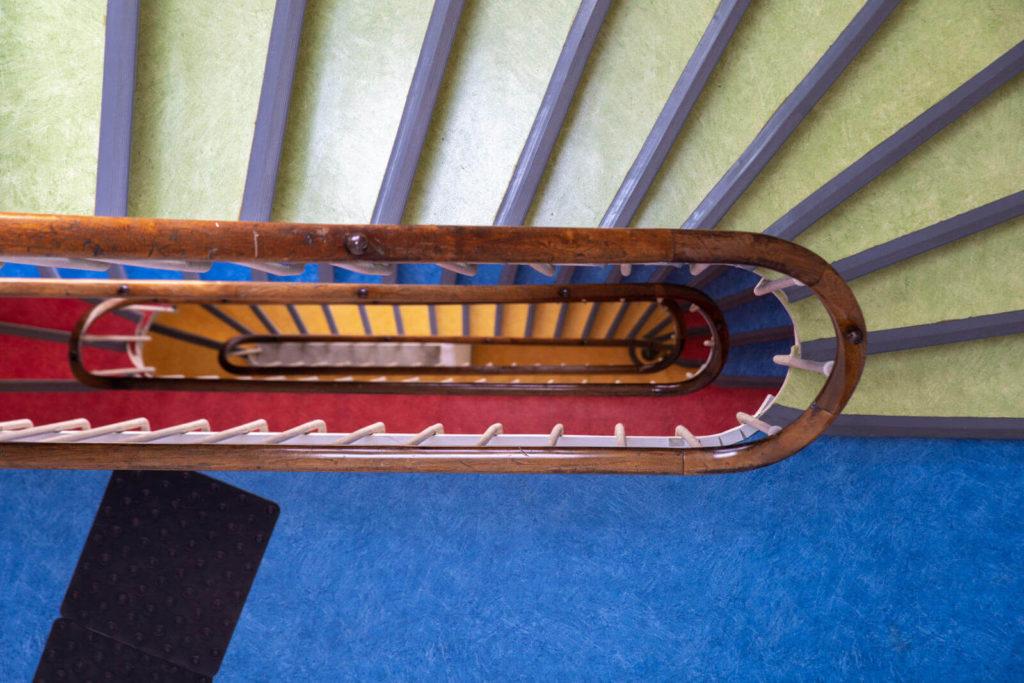 Vue plongeante de la cage d'escalier, avec une couleur distincte par étage