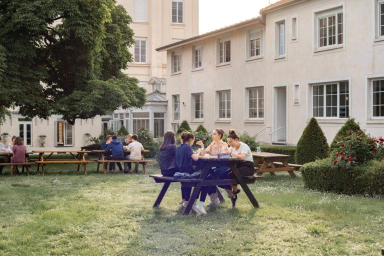 Etudiants en train de manger à l'extérieur, dans le jardin verdoyant du Foyer étudiant Les Enfants des Arts, près de Paris