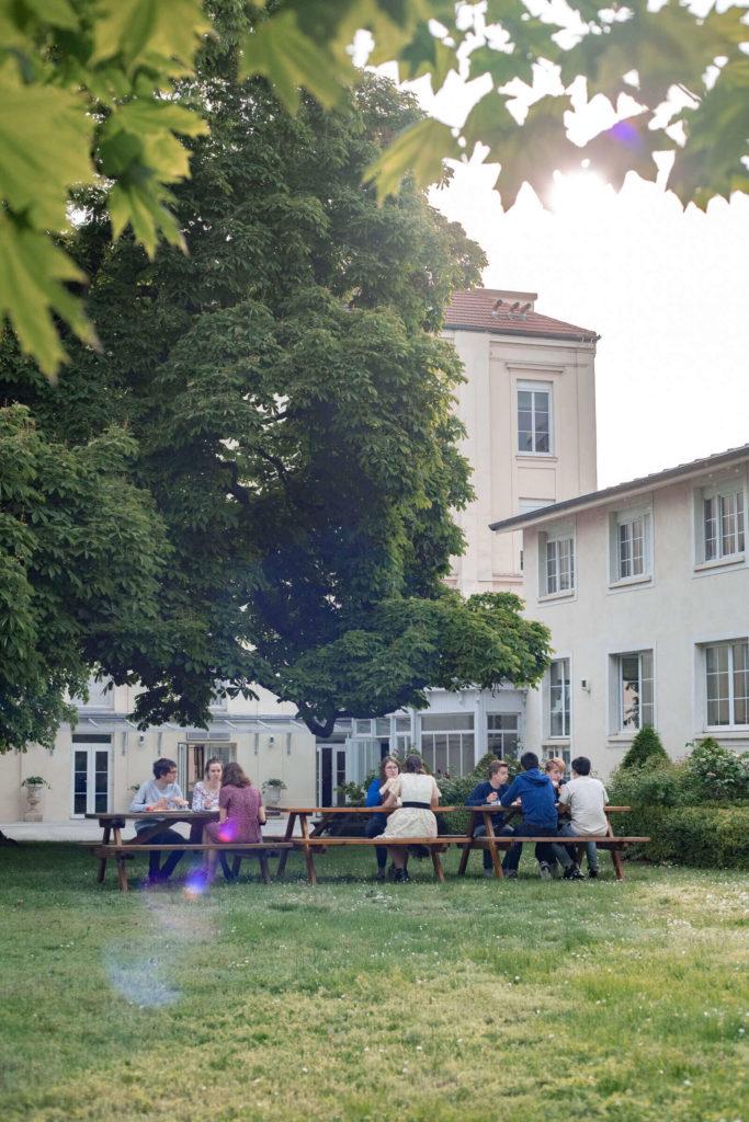 Neuf étudiants en train de manger à l'extérieur, dans le jardin verdoyant du Foyer étudiant Les Enfants des Arts
