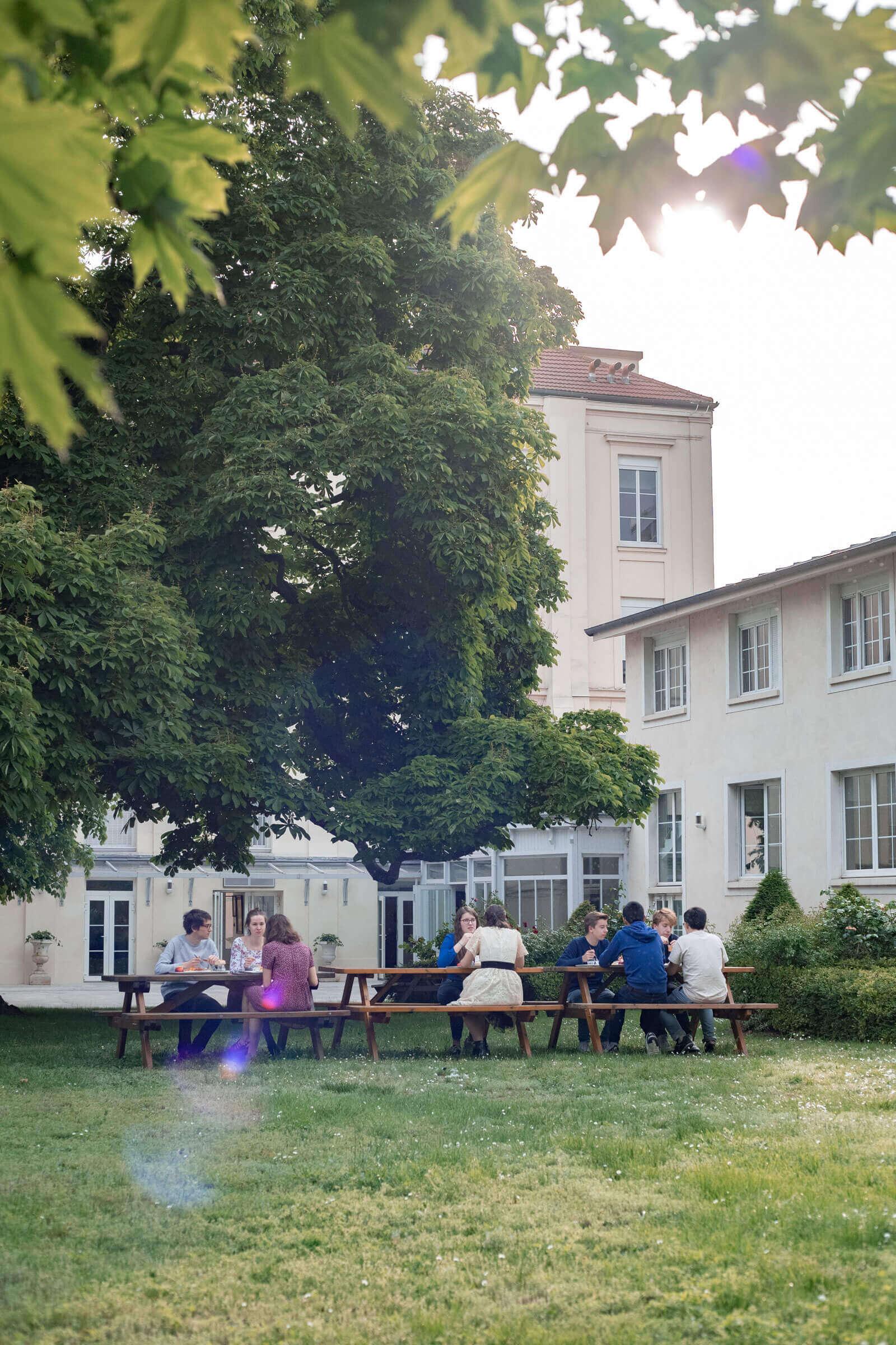 Neuf étudiants en train de manger à l'extérieur, dans le jardin verdoyant du Foyer Les Enfants des Arts