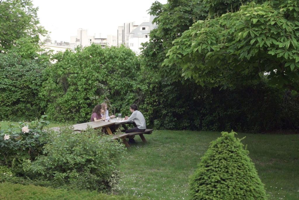 Trois personnes autour d'une table, dans le jardin verdoyant du Foyer étudiant Les Enfants des Arts